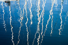 Sailboats reflexes on the marina. Saliboats mast reflected on the marina water in an Italian harbour Royalty Free Stock Image