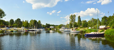 Sailboats river landscape. Panoramic view of sailboats marina, river landscape with sky reflection stock photography