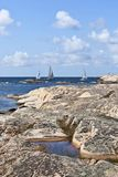 Sailboats at rocky coast royalty free stock image