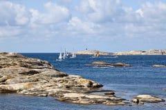 Sailboats at rocky coast Royalty Free Stock Images