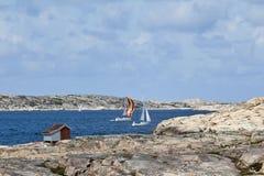 Sailboats at rocky coast royalty free stock photography