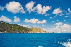 Sailboats sail in sea on cloudy blue sky in gustavia, st.barts. Sailing and yachting adventure. Summer vacation on. Tropical island. Water transport and vessel royalty free stock photos
