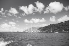 Sailboats sail in sea on cloudy blue sky in gustavia, st.barts. Sailing and yachting adventure. Summer vacation on. Tropical island. Water transport and vessel stock photo
