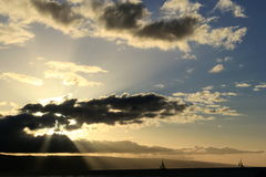 Sailboats. Sailing into the beautiful sunbeams in Maui stock images