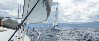 Sailboats sailing in regatta on the Mediterranean Sea in cloudy weather. Stock Photo