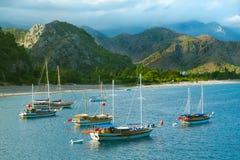 Sailboats at sea coast. Group of sailboats at anchor near mountainous sea shore Stock Photography
