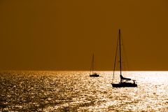 Sailboats silhouettes at dusk royalty free stock images