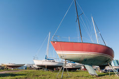 Sailboats on stands. On dry land awaiting repair stock image
