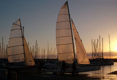 Sailboats at sunset. Two sailboats at sunset at the marina,with masts in the background stock image