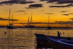 Sailboats at sunset on the Caribbean, Vieques Island, Puerto Rico. Orange sunset silhouette of small sailboats moored in Esperanza, off of Vieques Island, Puerto Royalty Free Stock Photos