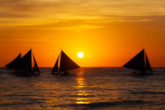 Sailboats at sunset on a tropical sea. Silhouette photo. Royalty Free Stock Photos