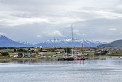 Sailboats in Ushuaia Harbor with snow covered mountains in the background. Sailboats moored in Ushuaia Harbor, Argentina, with snow covered mountains in the Stock Image