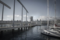 Sailboats and walking bridge in harbor. Barcelona, spain stock image
