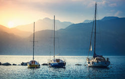 Sailers boats sailing by sea waves in evening sunset Stock Photos