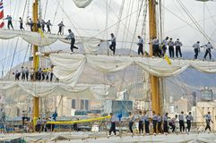 Sailors setting sails of three masted ship on foggy day Royalty Free Stock Image