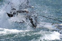 Sailing 003. Seas splash up and hit sailors while they race their boats Royalty Free Stock Photo