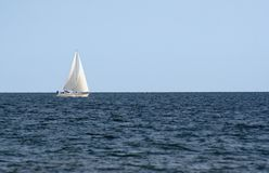 Sailing. A sailboat sailing on the open sea against the blue sky Stock Images