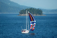 Sailing. A colorful sail boat passing by a tiny island Royalty Free Stock Photography