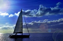 Sailing. A sailing boat is navigating with a blue sea and a blue sky Royalty Free Stock Photo