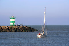 Sailing. Boat  past a lighthouse royalty free stock photography