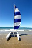 Sailing. On a beautiful summers beach resort day without a cloud in the sky a cataraman with a blue and whiote sail rocks backwards and forwards in the shallow Royalty Free Stock Photo