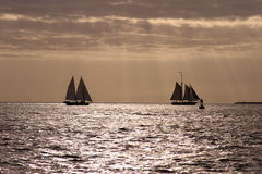 Sailing. Two Sailboats sailing on the ocean at sunset royalty free stock photos