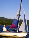 Sailing 4. Man in sailboat on lake with mountains in background royalty free stock images