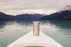 Sailing across lake Argentino. Detail of the the bow with white mountains in the back Royalty Free Stock Image