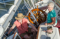 Sailing Action. A happy senior couple enjoys time together sailing on a lake on a fine summer day stock photography