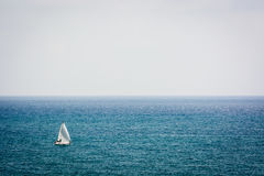 Sailing alone. A sailboat sailing by sea on a foggy day Stock Photos