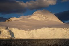 Antarctica calm orange midnight sunset on snowy mountain stock photography