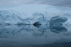 Antarctica glaciers reflect in mirror blue bay on cloudy day stock photos