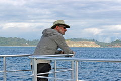 Sailing Away. A man enjoys the view from a boat as it sails away from the shore in Manuel Antonio, Costa Rica Stock Photography