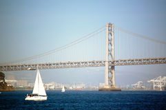 Sailing By The Bay Bridge. A Boat sailing past the Bay Bridge in San Francisco Bay, California Stock Image