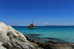 Sailing between the blue of the sky and the sea. Boat with tourists sailing on the bluish blue of the Aegean Sea Stock Photo