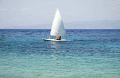 Sailing boat. A color landscape photo of a small white sailing boat moving across a beautiful blue ionian sea Royalty Free Stock Images
