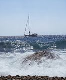 Sailing boat. Beautiful waves breaking on the rocks. Sailing boat is in the background stock images