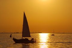 Sailing boat. At sunset with wind power in the background Stock Images