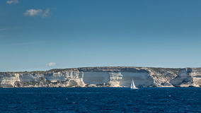 Sailing boat against white cliffs near Bonifacio in Corsica Stock Photography