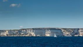 Sailing boat against white cliffs near Bonifacio in Corsica Stock Photography