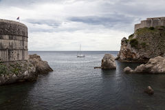 Sailing boat along the walls of Dubrovnik. Medieval city in the adriatic coast Stock Image