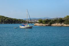 A sailing boat anchoring in a bay near Porto Heli, Peloponnese, Greece. Horizontal Royalty Free Stock Photography