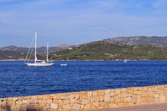Sailing boat in the bay. Beautiful panorama with a sailing boat in the bay with the hills in the background. This Photo was taken in Cannigione - Arzachena Gulf Royalty Free Stock Image