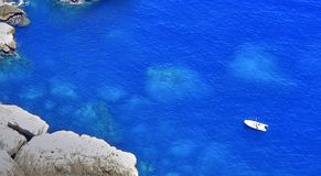Sailing boat in a bay on the island of Mallorca , rocks under th. Sailing boat in a bay on the island of Mallorca in lovely blue water with rocks under the Stock Image