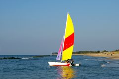 Sailing boat at beach. A single sailing boat near the coast line, colourful sail, some people on the beach. The Baltic Sea Royalty Free Stock Photo