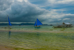 Sailing boat with a blue sail on a background of clouds , Boracay island, Philippines Stock Photo