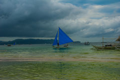 Sailing boat with a blue sail on a background of clouds , Boracay island, Philippines Royalty Free Stock Photo