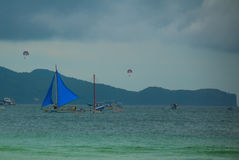 Sailing boat with a blue sail on a background of clouds , Boracay island, Philippines Royalty Free Stock Images