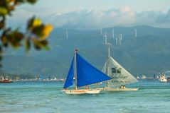Sailing boat with a blue sail on a background of clouds , Boracay island, Philippines Stock Photos