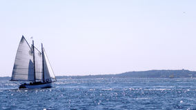 Sailing boat on blue shining sea under sunshine. Magnificent sea view Stock Photos
